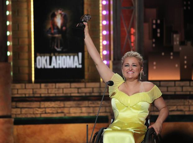 השחקנית אלי סטרוקר בכיסא גלגלים, מניפה את הפרס על הבמה