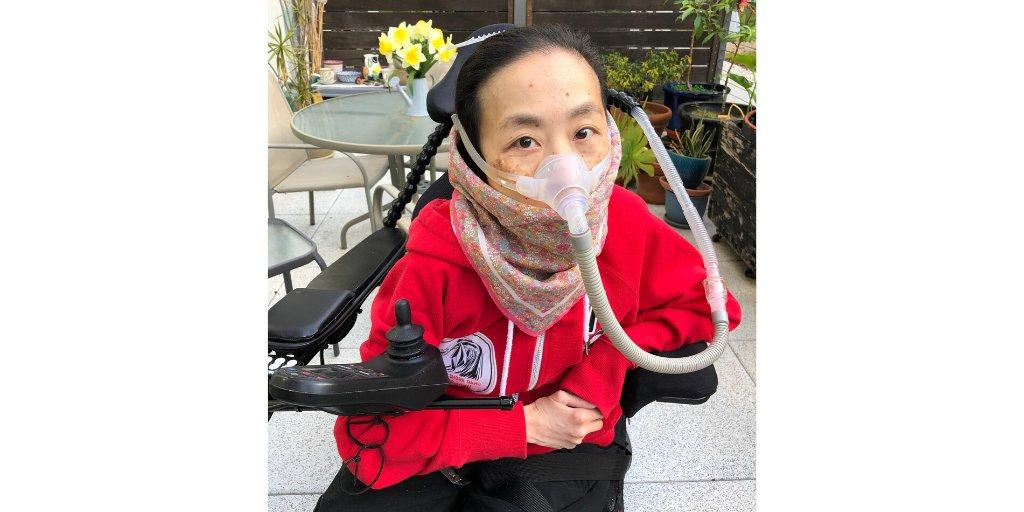 אליס וונג, יושבת בכיסא גלגלים ממונע ועוטה מסכת חמצן
