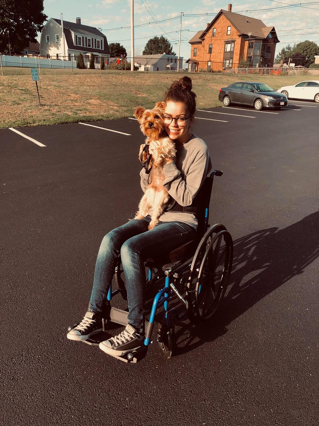 ג'ניפר ווירץ, יושבת בכיסא גלגלים ומחזיקה כלב קטן