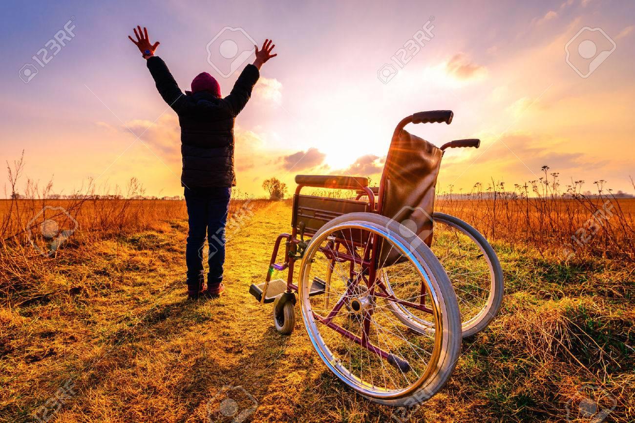 תמונה מאתר 123RF- נכה קמה מכיסא גלגלים ומניפה ידיים בניצחון