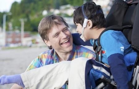 ילד עם מוגבלות בכיסא גלגלים, אבא רוכן לידו ושניהם מחייכים