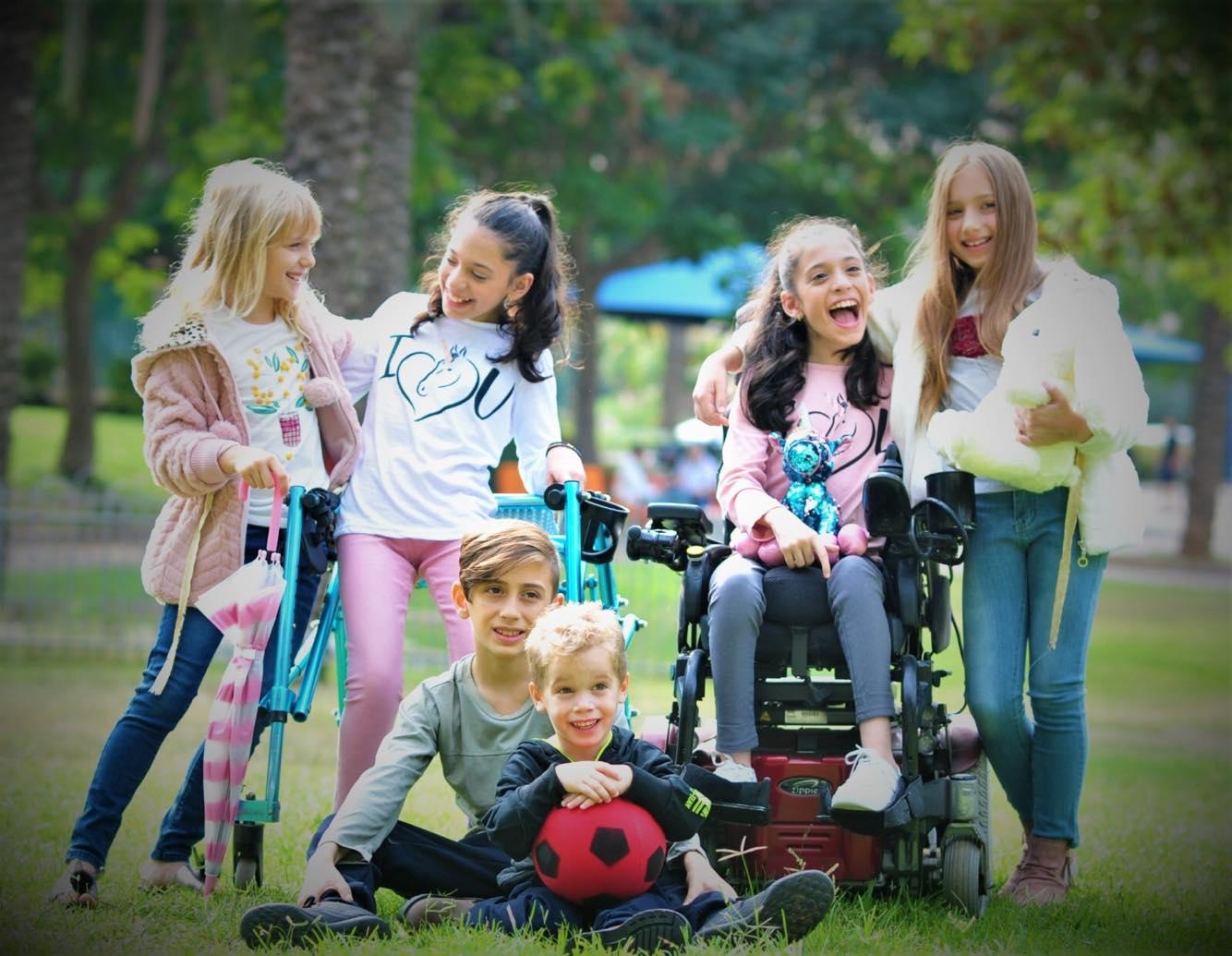 צילום מתוך הקמפיין: ילדה בכיסא ממונע, ילדה עם הליכון ועוד שלושה ילדים ללא מוגבלות, על הדשא