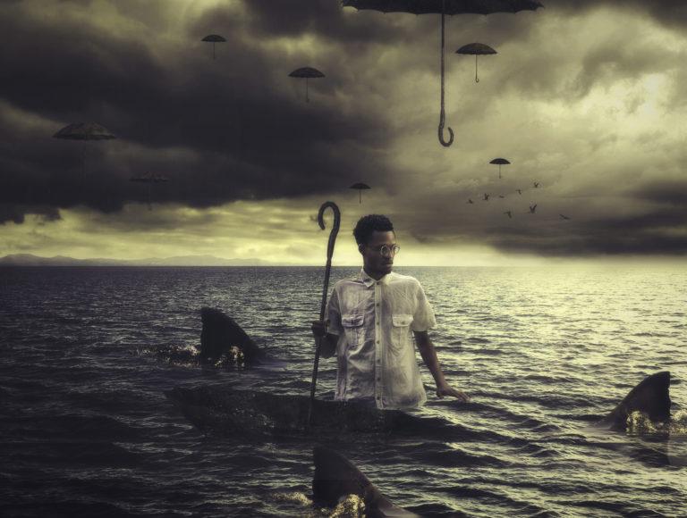 פורטרט עצמי, האמן עומד בלב ים ביום סוער, סביבו סנפירים של כרישים