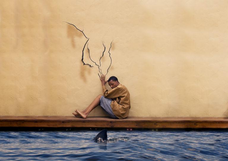 דיוקן עצמי, האמן יושב על משטח עץ ליד מים שבו סנפיר של כריש, על הקיר סימני הציפורניים המפוחדות שלו
