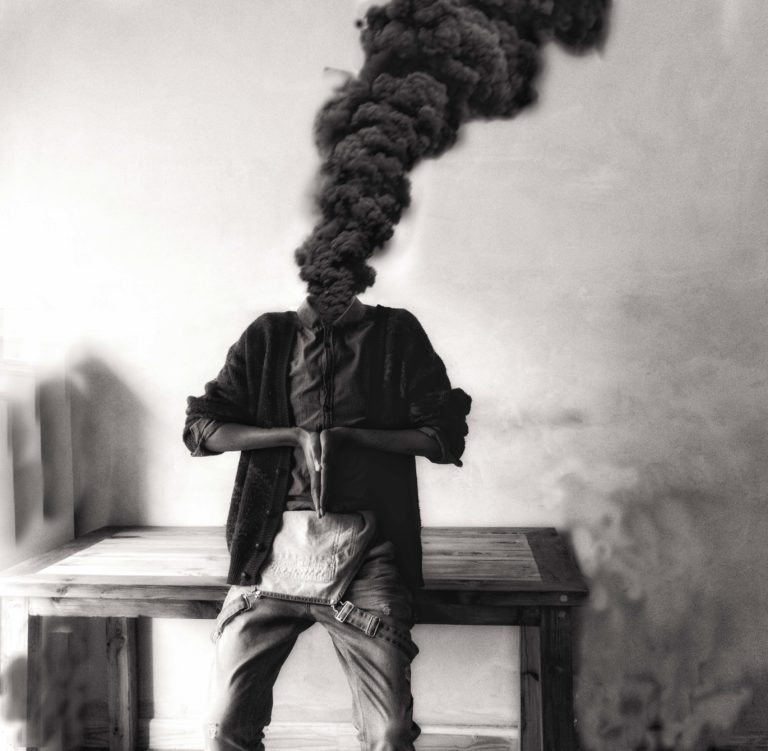 תמונת שחור-לבן, האמן נשען על שולחן כשבמקום הראש, מיתמר ענן עבה של עשן