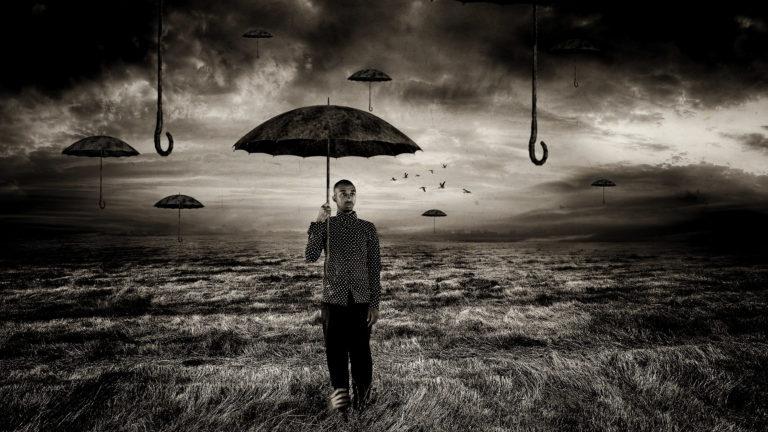 האמן עומד בשדה עם מטריה ביום קודר, ועוד כמה מטריות מרחפות באוויר