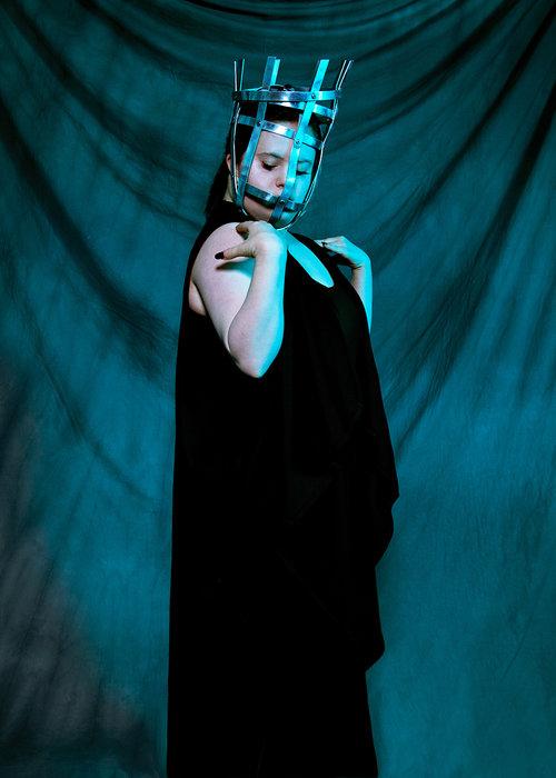 צעירה עם תסמונת דאון לבושה בשמלה שחורה ומסיכת ברזל